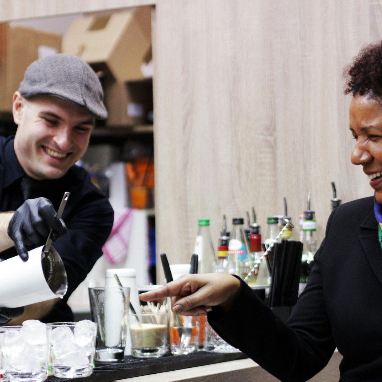 Barkeeper an der Messe Berlin. Gäste lächeln